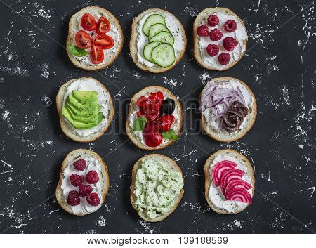 Variety of sandwiches - sandwiches with cheese tomatoes anchovies roasted peppers raspberries avocado bean pate cucumber olives. On a blue background top view.