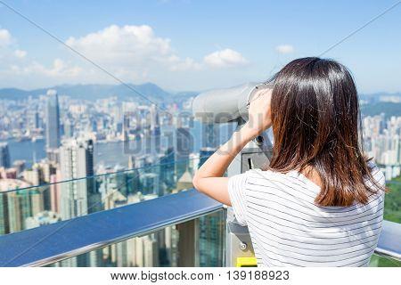 Tourist using binocular looking though Hong Kong cityscape