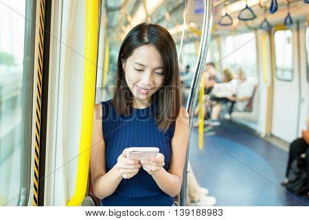 Woman sending sms on cellphone inside MTR in Hong Kong