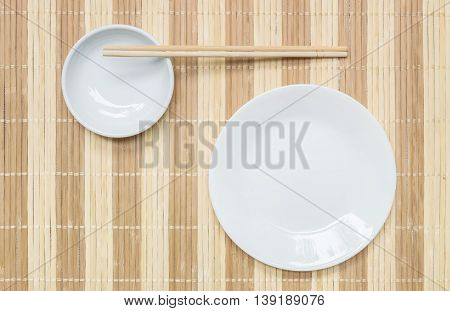 Closeup white ceramic dish and chalice with wood chopsticks on wood mat textured background on dining table in top view