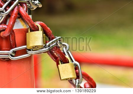 closed padlock with key and many chains