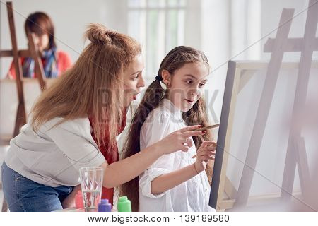 girl with teacher painting at easel in school.