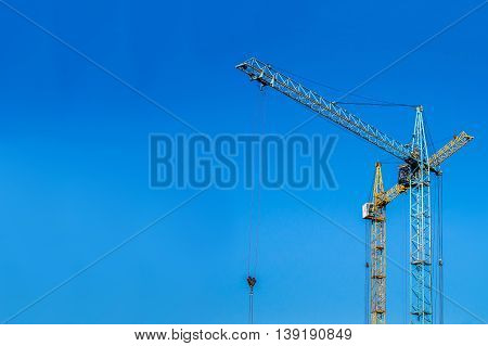 Two cranes against the blue sky. Blue and yellow crane at the construction site.