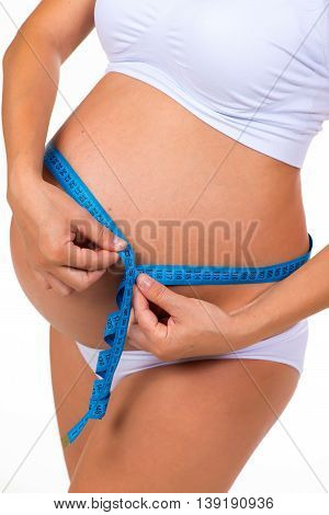 Measuring girth tummy with meter tape. Pregnancy. Pregnant belly