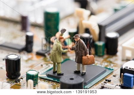 Miniature Person Are Shaking Hands On A Computer Motherboard