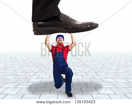 Businessman trying to trample a worker