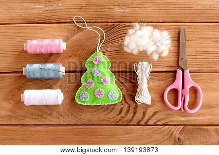Felt Christmas tree ornament decor on a wooden table. Christmas DIY idea. Thread kit, cord, hollofayber, scissors on a wooden table. Top view. Step