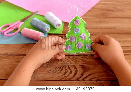 Child holding a felt Christmas tree in his hands. Green fabric Christmas tree decorated with pink and blue balls. New year crafts idea for children. Felt sheets, scissors, thread on wooden table