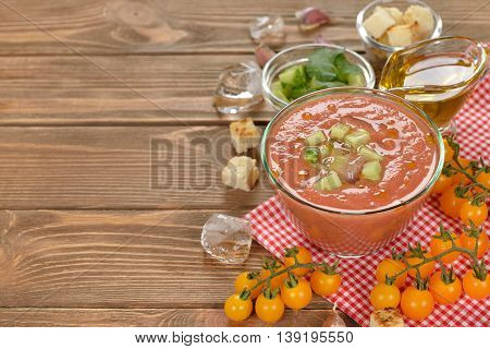 Cold soup gazpacho with yellow tomatoes on a brown background