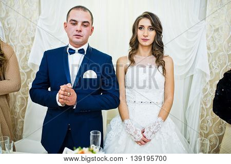 Wedding Couple At The Table On Restaurant, Hands Folded For Prayer
