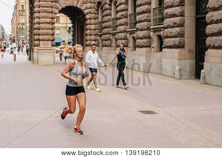 Stockholm, Sweden - July 30, 2014: Young Attractive Girl Running Near The Royal Palace In Gamla Stan.