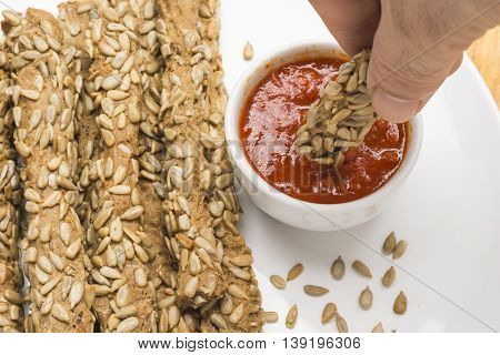 Dipping a breadstick with sunflower seeds in sauce