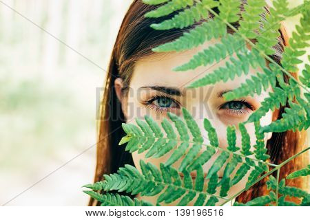 Close Up Portrait Of A Young Happy Beauty Red Hair Girl Woman Holding Fern Leaf Up To Face In Summer Park Forest