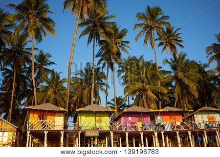 Colorful huts on the sandy beach with palm trees background in Goa, India