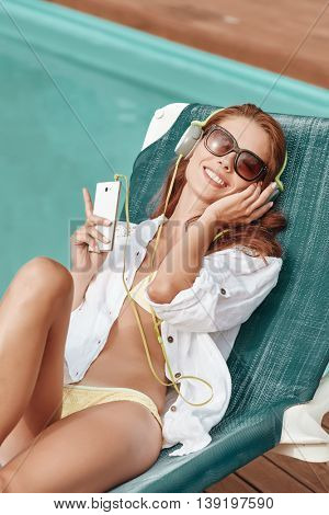 Portrait of beautiful girl listening to music in the swimming pool.