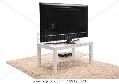 Rear view shot of a modern black flat screen TV on a white wooden TV unit isolated on white background