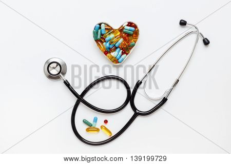 stethoscope on a white background with pills in the shape of heart isolated top view
