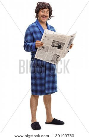 Full length portrait of an excited young man in a blue bathrobe holding a newspaper isolated on a white background