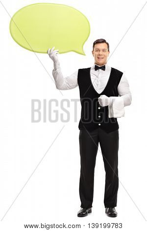 Full length vertical shot of a young male waiter holding a big yellow speech bubble isolated on white background