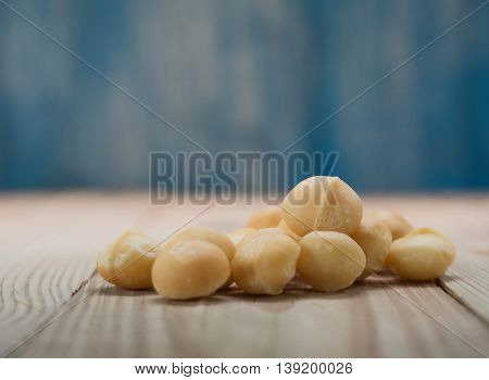 Macadamia on wooden floor with blue wooden background blur.Focus on macadamia.