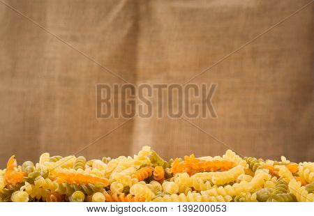 Pasta spirals with sackcloth background.Selective focus on front pasta spirals.