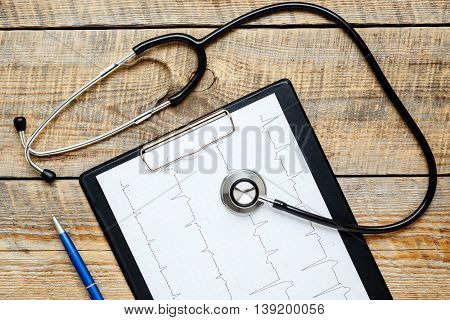 new stethoscope on wooden table with cardiogram close up