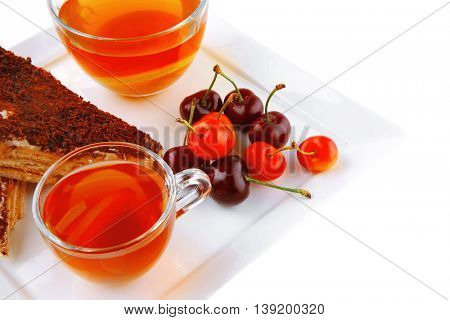 english cake and tea with cherry on white plate