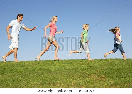 Young family, parents with children,  running through field