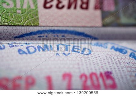 Passport stamp with a caption Admitted in blue ink as a part of Visa page