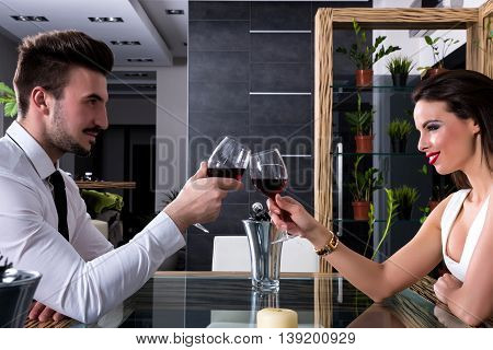 Young couple clinking with glasses of red wine