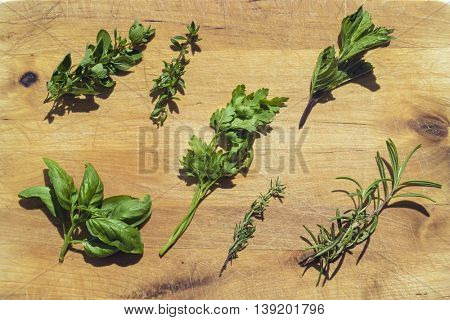 Fresh herbs on wooden cutting board. Flat lay food on table.