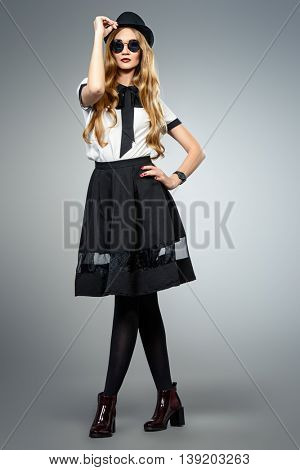 Full length portrait of a fashion model. Beautiful young woman wearing pretty blouse and skirt. Studio portrait over gray background.