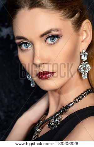Close-up portrait of a beautiful young woman wearing earrings and necklace with gems. Jewellery. Beauty, fashion. Studio shot.