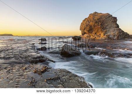 High tide current passing through rocks at Currumbin Rock at sunset, Gold Coast