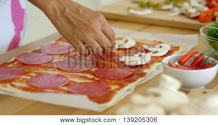 Woman making a homemade salami and mushroom pizza