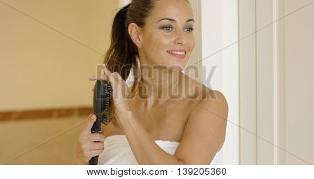 Young woman brushing her long hair