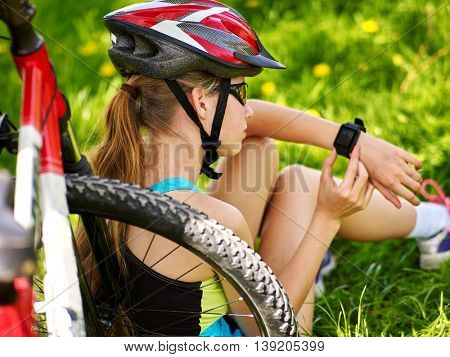 Bicycling girl. Bicyclist girl in bicyclist helmet watch on smart watch. Girl counts pulse after bicycle training. Bicycling is good for health. Top view. Back view.