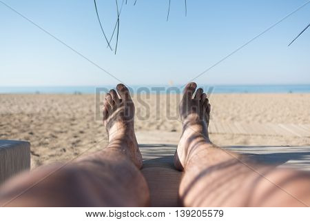 Male feet on lounge first person view from bungalow on the sea with sand beach