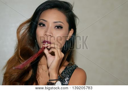 Portrait of pretty whistling Vietnamese young woman