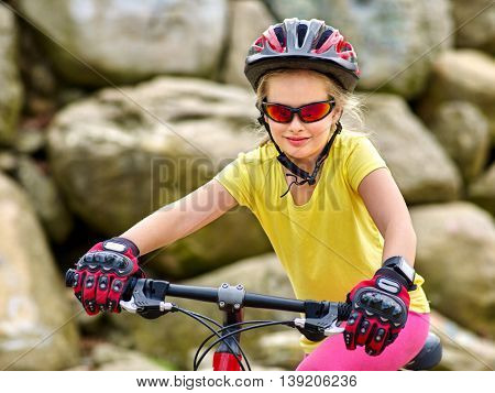 Portrait of child girl rides bicycle into mountains. Child girl wearing helmet and gloves on bicycle in mountaineering . Mountaineering is good for health. Happy child.
