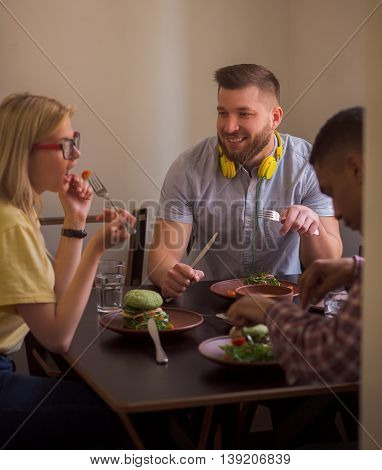 Portrait of smiling man communicating with his friends eating healthy vegan dishes. Happy friends spending their free time in vegan restaurant or cafe.