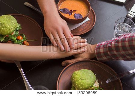 Picture of business people sitting in vegan restaurant and showing unity of their team. Team work of realbusiness people.
