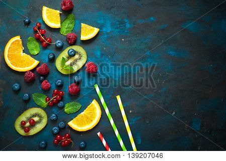 Fresh summer berries and fruits on dark background. Healthy food concept. Flat lay. Fruit background.