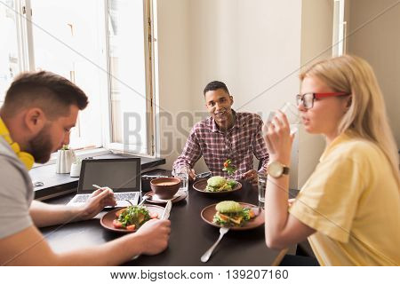 Portrait of happy businessman looking at camera while his partners communicating about business in vegan restaurant or cafe. Team work concept.