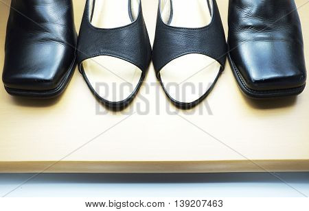 Close up of woman leather shoe and man leather shoe on wooden floor.