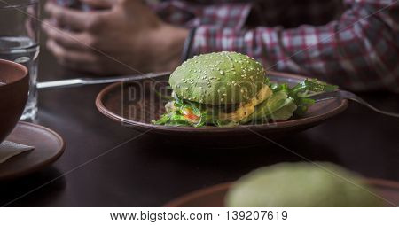 Vegan restaurant or cafe. Picture of vegan dish represented on plate. Vegan hamburger and cherry tomatoes are nice idea for vegan person.