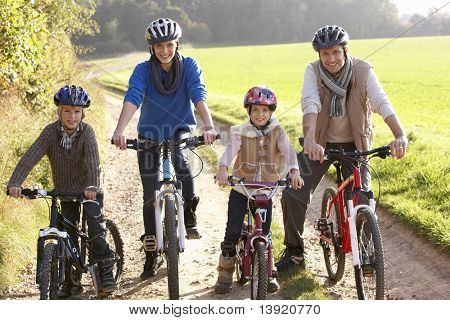 Young family pose with  bikes in park
