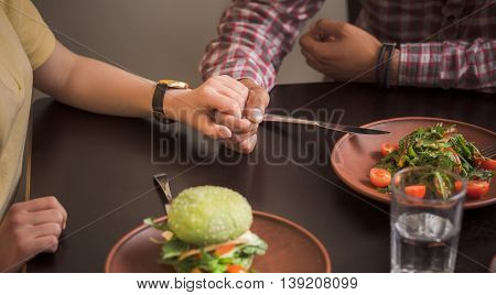 Happy couple spending time in vegan restaurant or cafe. Happy couple eating vegan dishes in vegan restaurant or cafe.