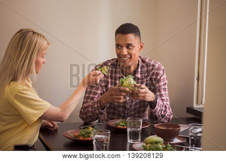 People looking at each other while sitting at table. Happy couple eating vegan dishes in vegan restaurant or cafe.