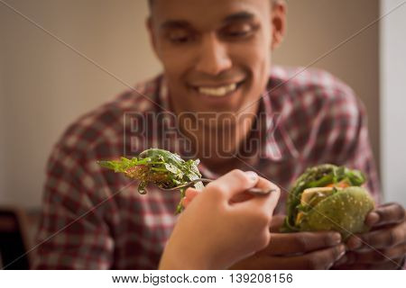 Closeup picture of lady feeding her boy-friend with vegan salad. Happy couple spending free time in vegan restaurant or cafe.